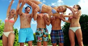 Grupo de amigos que se divierten en el poolside almacen de metraje de vídeo