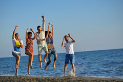 Grupo de amigos que se divierten que camina abajo de la playa en la puesta del sol Imagen de archivo libre de regalías