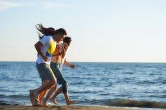 Grupo de amigos que se divierten que camina abajo de la playa en la puesta del sol Foto de archivo