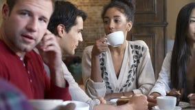 Grupo de amigos que se encuentran en el restaurante de Café almacen de video