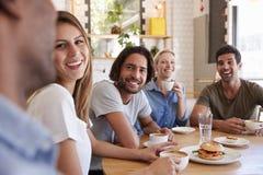 Grupo de amigos que se encuentran para el almuerzo en cafetería foto de archivo libre de regalías