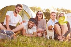 Grupo de amigos que se relajan fuera de las tiendas en acampada imagenes de archivo