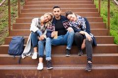 Grupo de amigos que se sientan afuera en las escaleras imagen de archivo libre de regalías