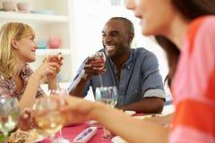 Grupo de amigos que se sientan alrededor de la tabla que tiene partido de cena Imagen de archivo libre de regalías