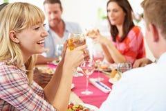 Grupo de amigos que se sientan alrededor de la tabla que tiene partido de cena imagenes de archivo