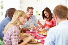 Grupo de amigos que se sientan alrededor de la tabla que tiene partido de cena fotografía de archivo