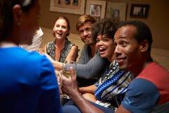 Grupo de amigos que se sientan alrededor de una tabla en el partido de casa foto de archivo