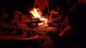 Grupo de amigos que se sientan cerca de hoguera en la noche en la playa y que cuelgan hacia fuera 4k UHD metrajes