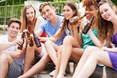 Grupo de amigos que se sientan con las cervezas en sus manos Foto de archivo libre de regalías