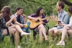 Grupo de amigos que se sientan en círculo hacia fuera en parque imagen de archivo libre de regalías