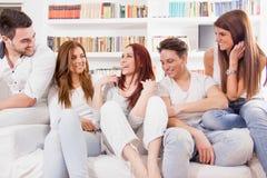 Grupo de amigos que se sientan en el sofá que habla y que sonríe Foto de archivo