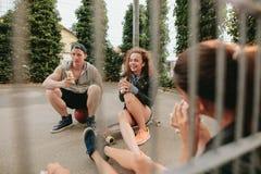 Grupo de amigos que se sientan en la cancha de básquet y que se divierten Imágenes de archivo libres de regalías