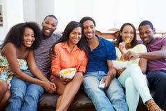 Grupo de amigos que se sientan en Sofa Watching TV junto Imagen de archivo libre de regalías