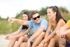 Grupo de amigos que señalan en alguna parte en la playa Imagen de archivo