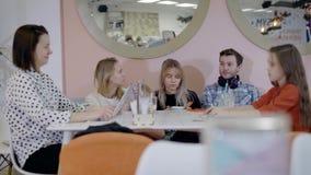 Grupo de amigos que sentam-se casualy no café junto, encontrando-se nos fins de semana vídeos de arquivo