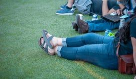 Grupo de amigos que sentam-se na grama com bebidas e laptop fotografia de stock royalty free