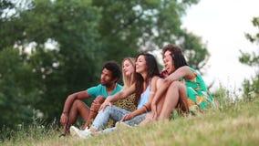 Grupo de amigos que sentam-se na grama que tem uma boa estadia filme