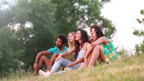 Grupo de amigos que sentam-se na grama que tem uma boa estadia vídeos de arquivo
