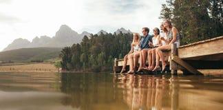 Grupo de amigos que sentam-se na parte traseira de uma picareta acima do carro fotografia de stock