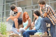Grupo de amigos que sientan el banco fuera de la universidad Imágenes de archivo libres de regalías