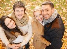 Grupo de amigos que têm o divertimento no parque do outono imagem de stock royalty free