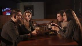 Grupo de amigos que têm o jantar no café video estoque