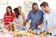 Grupo de amigos que têm o partido de jantar em casa imagem de stock royalty free