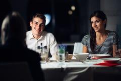 Grupo de amigos que têm um jantar em um restaurante Data dobro Noite atrativa dos povos para fora, jantando em um hotel Povos na  fotografia de stock