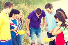 Grupo de amigos que tienen comida campestre en la playa Foto de archivo