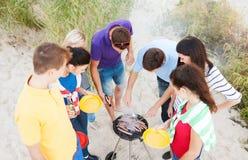 Grupo de amigos que tienen comida campestre y que hacen la barbacoa Imágenes de archivo libres de regalías