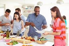 Grupo de amigos que tienen partido de cena en casa Imagenes de archivo