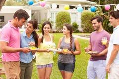 Grupo de amigos que tienen partido en patio trasero en casa Fotografía de archivo