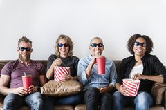 Grupo de amigos que tienen película de observación de la diversión junto imagenes de archivo