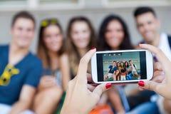 Grupo de amigos que tomam fotos com um smartphone na rua Imagem de Stock Royalty Free