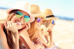 Grupo de amigos que tomam sol na praia Fotos de Stock Royalty Free