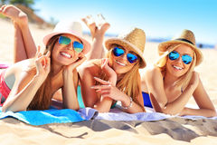 Grupo de amigos que tomam sol na praia Fotografia de Stock Royalty Free