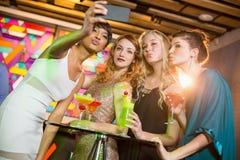 Grupo de amigos que toman el selfie del teléfono móvil mientras que teniendo cóctel Imagen de archivo