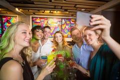 Grupo de amigos que toman el selfie del teléfono móvil mientras que teniendo cóctel Foto de archivo