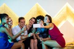 Grupo de amigos que toman el selfie mientras que comiendo vidrios de champán Foto de archivo libre de regalías