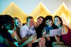 Grupo de amigos que toman el selfie mientras que comiendo vidrios de champán Fotos de archivo libres de regalías