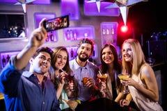Grupo de amigos que toman el selfie mientras que teniendo vidrios del cóctel Foto de archivo