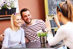 Grupo de amigos que toman imágenes en café imagen de archivo