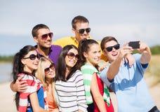 Grupo de amigos que toman la imagen con smartphone Fotografía de archivo libre de regalías