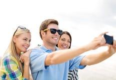 Grupo de amigos que toman la imagen con smartphone Fotografía de archivo