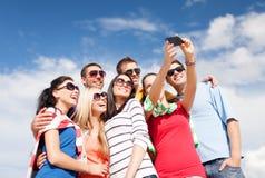 Grupo de amigos que toman la imagen con smartphone Fotos de archivo