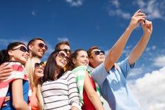 Grupo de amigos que toman la imagen con smartphone Imagen de archivo