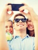 Grupo de amigos que toman la imagen con smartphone Foto de archivo