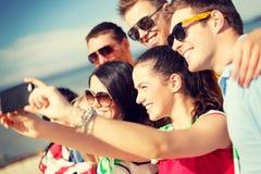 Grupo de amigos que toman la imagen con smartphone Imágenes de archivo libres de regalías