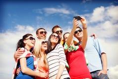 Grupo de amigos que toman la imagen con smartphone Fotos de archivo libres de regalías