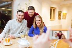 Grupo de amigos que toman la imagen con smartphone Foto de archivo libre de regalías
